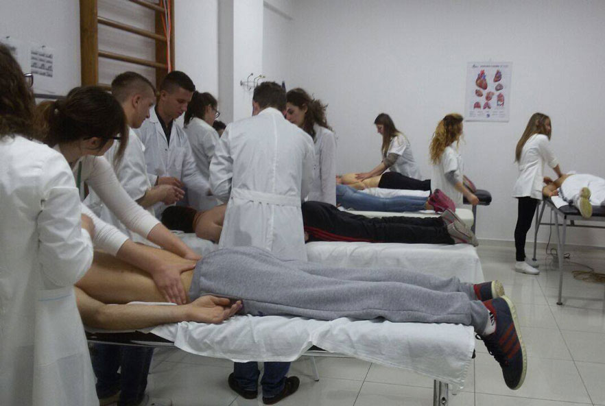 Physiotherapists work on patients lying on a table