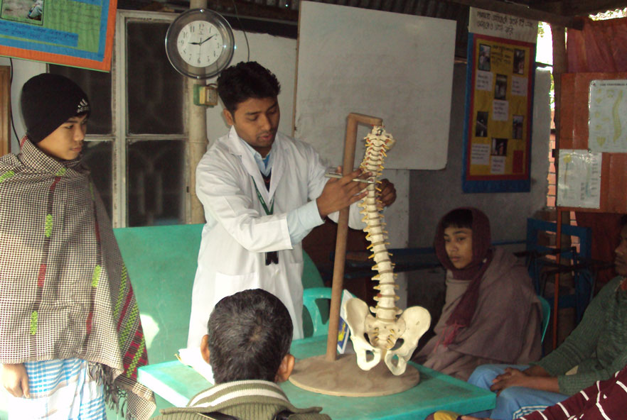 A man points to a model of a spine in a group of students