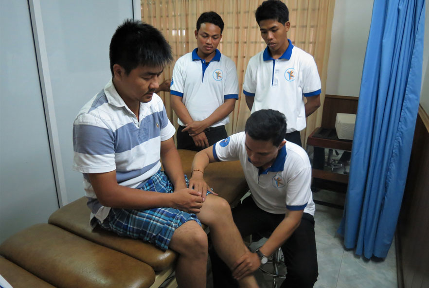 A physiotherapist examines a patient's leg
