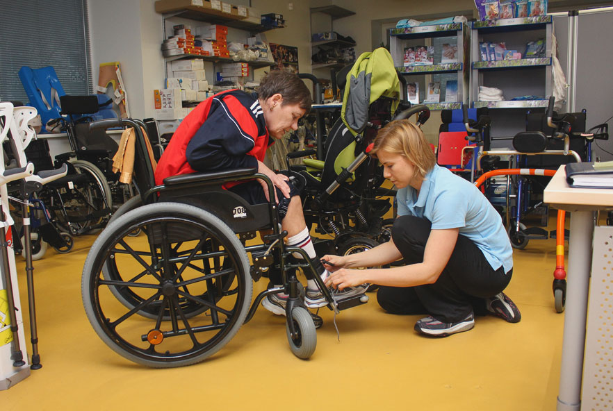 A physiotherapist attends to a person in a wheelchair