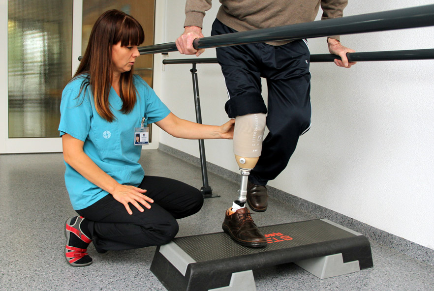A physiotherapist makes adjustments to a patient's prosthetic leg