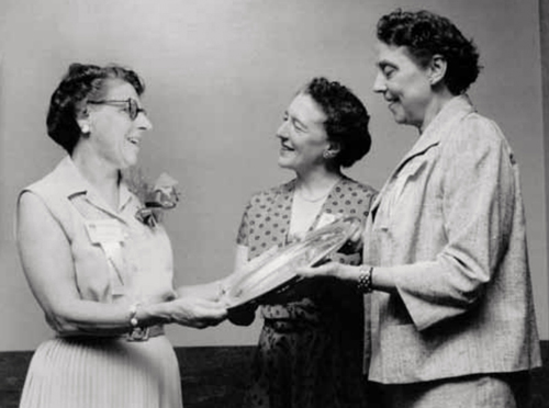 President Mildred Elson is presented with a salver by two women standing next to her.