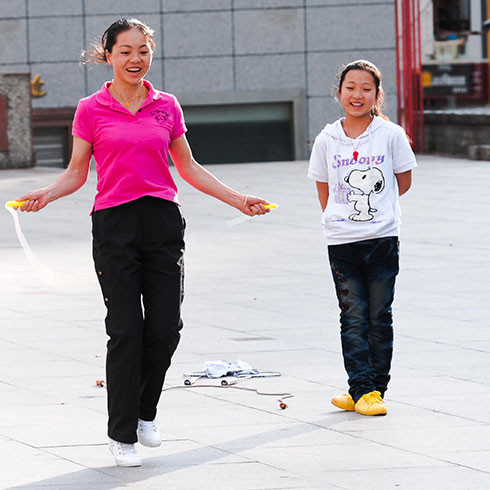 A photo of a young woman skipping