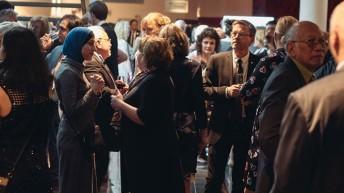 Orang-orang berkumpul untuk berbicara pada jamuan makan malam penghargaan