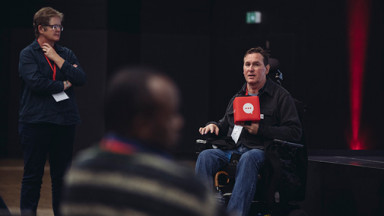 A man in a wheelchair talks to the audience
